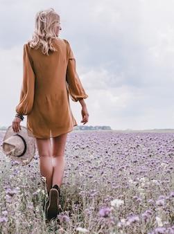 Smukłe nogi. ręce dziewczyny trzyma słomkowy kapelusz