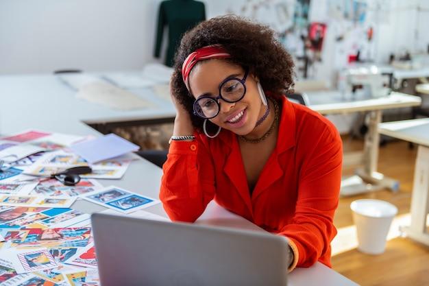 Smukły laptop. zdziwiona efektowna pani drapiąc się po głowie i obserwująca swój projekt prezentowany na ekranie swojego laptopa