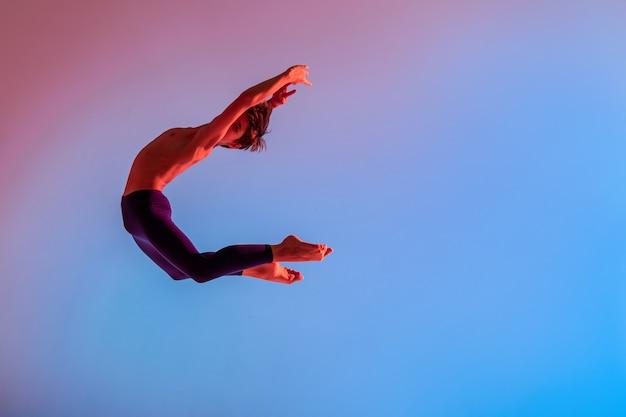 Smukły Nastolatek-baletnica Skacze Boso Pod Kolorowym światłem. Premium Zdjęcia
