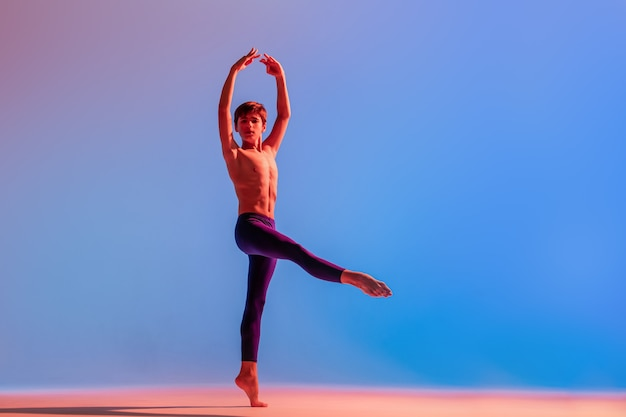 Smukły nastoletni tancerz baletowy tańczy boso w kolorowym świetle.