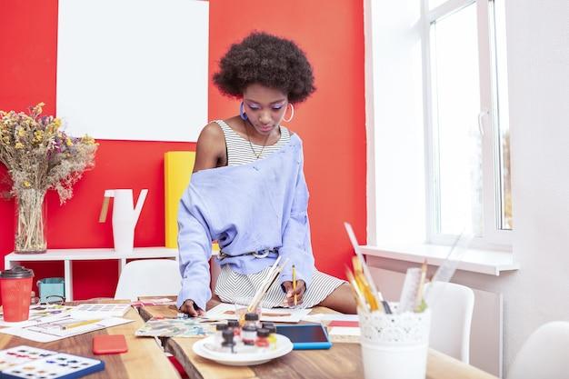 Smukły projektant. smukły, atrakcyjny projektant siedzi przy stole i rysuje szkice do nowego projektu