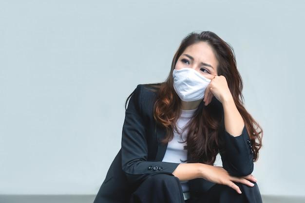 Smutek azjatycka bizneswoman zmęczona i siedząca na podłodze jako utrata pracy w kryzysie koronawirusa powodująca awarię bezrobocia na białej ścianie z maską na twarz