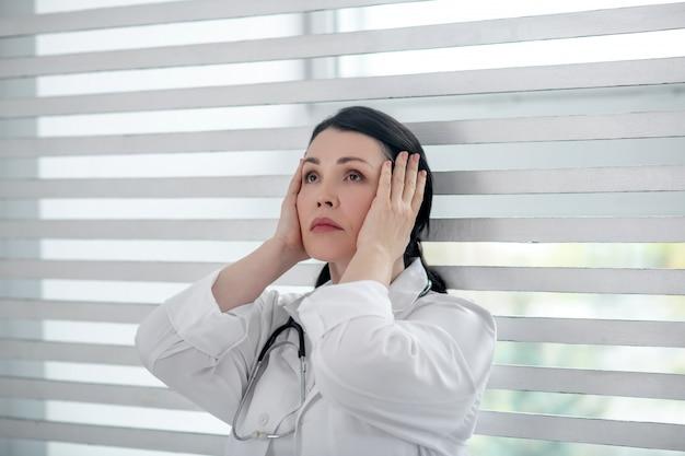 Smutek. brunetka kobieta w białym fartuchu lekarskim ze stetoskopem na szyi, patrząc w górę, ręce przy głowie, zamyślony smutny.