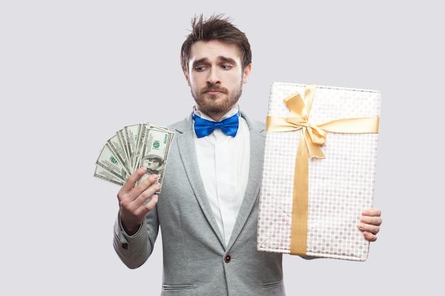 Smutek młody brodaty mężczyzna w szarym garniturze i niebieskiej muszce stoi i myśli, że nie chcesz wydawać dużo dolarów na duże pudełko z żółtą kokardą. wewnątrz, na białym tle, studio strzał, szare tło