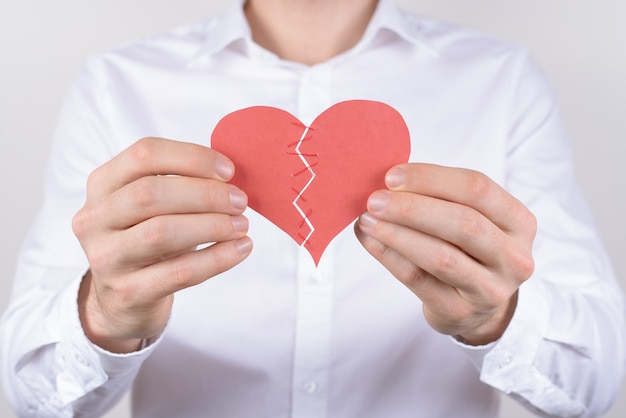 Smutek smutny niezadowolony zdenerwowany negatywna koncepcja. przycięte zbliżenie zdjęcia zmęczonego, wyczerpanego faceta, który próbuje połączyć, połączyć, zawiązać dwie części złamanego serca na białym tle szarym tle