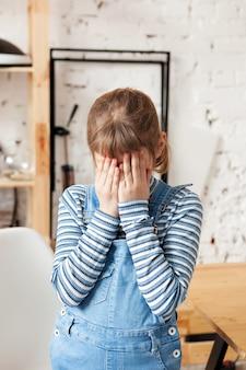 Smutna 8-letnia dziewczynka w kombinezonie zakrywającym twarz rękami