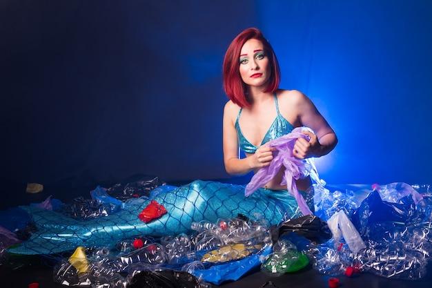 Smutna bajkowa syrenka w zanieczyszczonym oceanie.