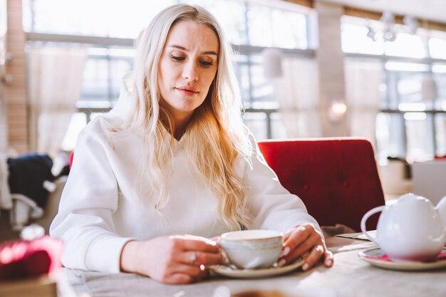 Smutna blond kobieta w średnim wieku siedzi samotnie w kawiarni przy filiżance herbaty lub kawy.