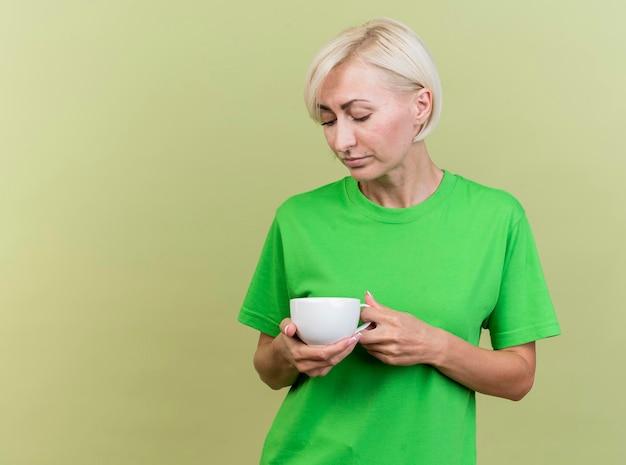 Smutna blond słowiańska kobieta w średnim wieku, trzymając i patrząc na filiżankę herbaty na białym tle na oliwkowej ścianie zielonej z miejsca na kopię