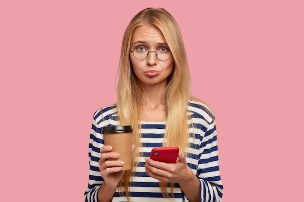 Smutna blondynka z obraźliwym wyrazem twarzy, zaciska usta z niezadowoleniem, gdy otrzymuje złą wiadomość