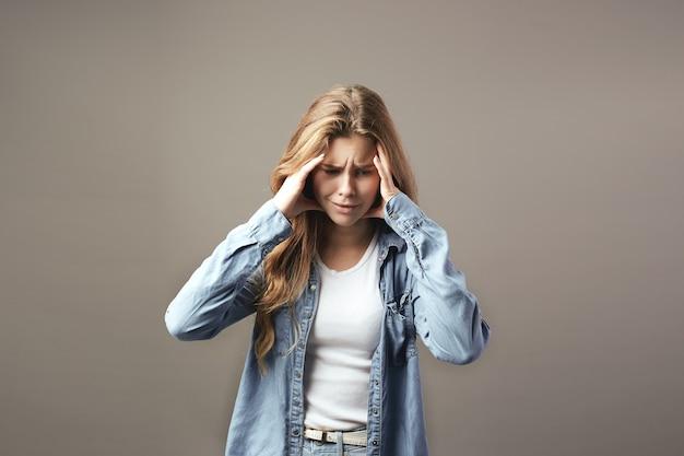 Smutna brązowowłosa dziewczyna ubrana w białą koszulkę i dżinsy trzyma ręce na głowie na szarym tle.