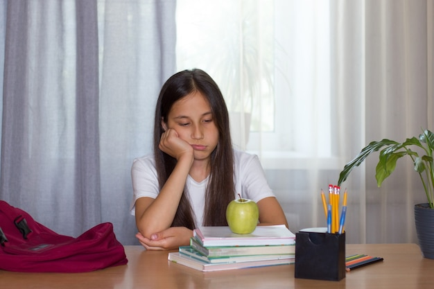 Smutna brunetka siedzi w domu nad książkami, na których widnieje jabłko powrót do koncepcji szkoły