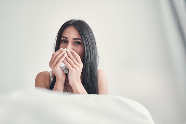 Smutna brunetka wyciera nos będąc na samotności w domu, siedząc na łóżku