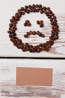 Smutna buźka wykonana z ziaren kawy i pustego papieru beżowego. białe drewniane deski na powierzchni.