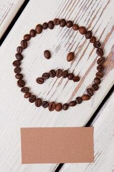 Smutna buźka z ziaren kawy. beżowy papier na lato na białych drewnianych deskach.