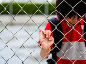 Smutna chłopiec za siatki ogrodzeniowe