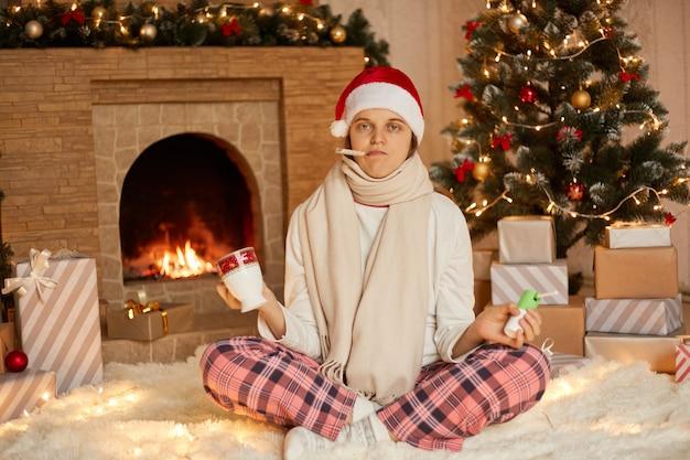 Smutna chora dziewczyna z termometrem w ustach na święta bożego narodzenia picia herbaty