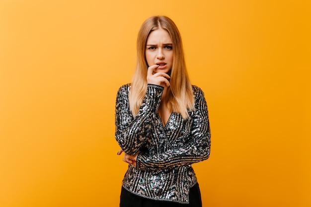Smutna czarująca kobieta w blasku kurtce pozowanie w studio. wspaniała zdenerwowana ślepa kobieta stojąca na pomarańczowo.