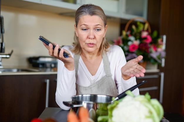 Smutna dojrzała kobieta w kuchni przygotowuje jedzenie i trzyma inteligentny telefon