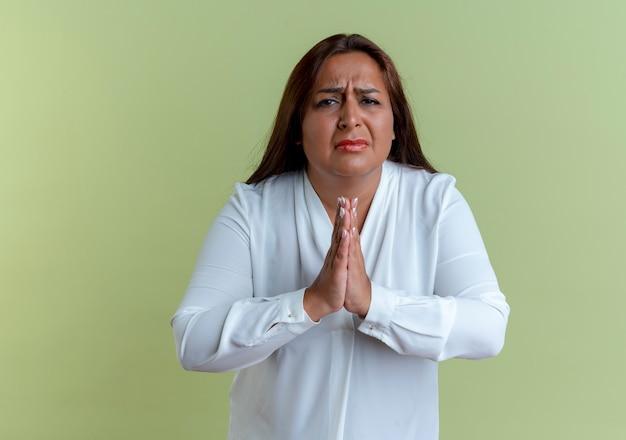 Smutna dorywczo kaukaski kobieta w średnim wieku pokazująca módl się gest na białym tle na oliwkowej ścianie