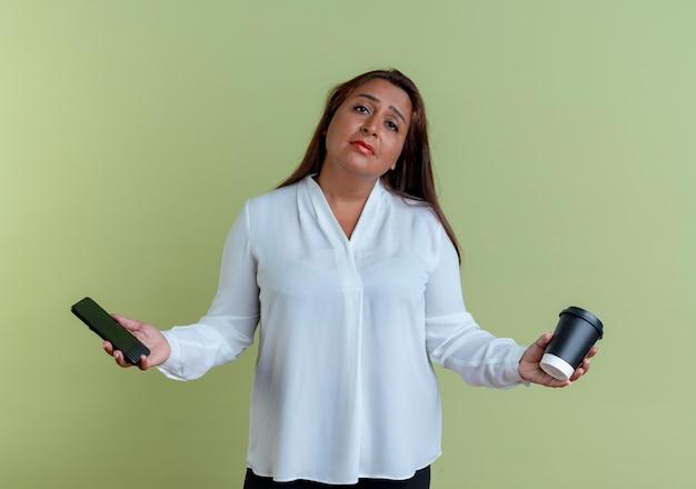 Smutna dorywczo kaukaski kobieta w średnim wieku trzymając telefon z filiżanką kawy na białym tle na oliwkowej ścianie