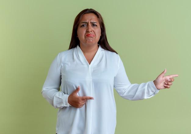 Smutna, dorywczo kaukaski kobieta w średnim wieku wskazuje na bok na białym tle na oliwkowej ścianie z miejsca na kopię