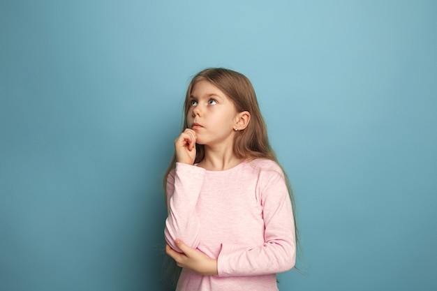 Smutna dziewczyna na niebieskim tle studio. wyraz twarzy i koncepcja emocji ludzi.