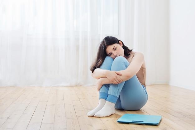 Smutna dziewczyna nastolatka na podłodze z wagą
