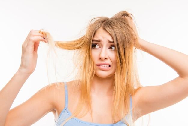Smutna dziewczyna patrząc na jej zniszczone włosy
