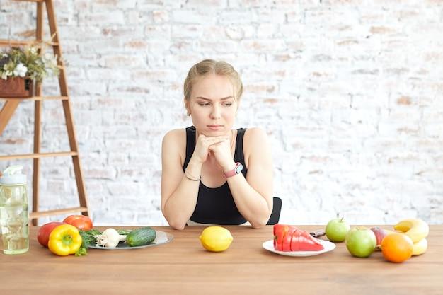 Smutna dziewczyna patrzy na leżące na stole warzywa. zmieniają się nawyki żywieniowe. smutna kobieta nie znosi diety wegetariańskiej.