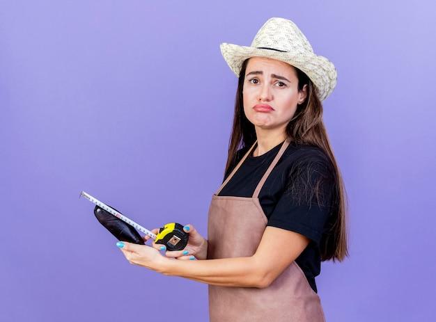 Smutna dziewczyna piękny ogrodnik w mundurze na sobie kapelusz ogrodniczy środek bakłażan z centymetrem na białym tle na niebieskim tle