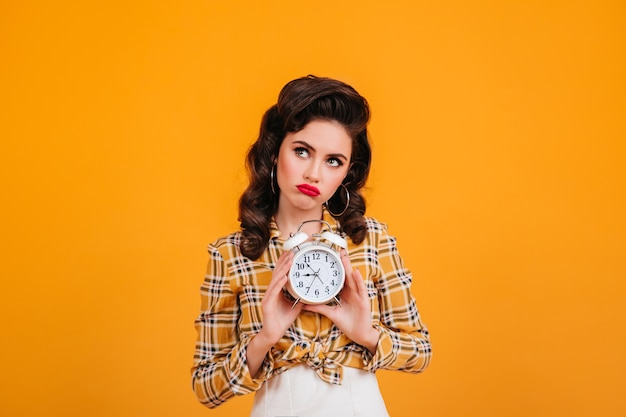 Smutna dziewczyna pinup gospodarstwa zegar. studio strzałów zamyślony młoda kobieta w żółtej koszuli w kratkę.