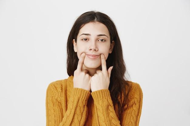 Smutna dziewczyna próbuje wyciągnąć szczęśliwy uśmiech, przesuwając kąciki ust w górę z niechętną twarzą
