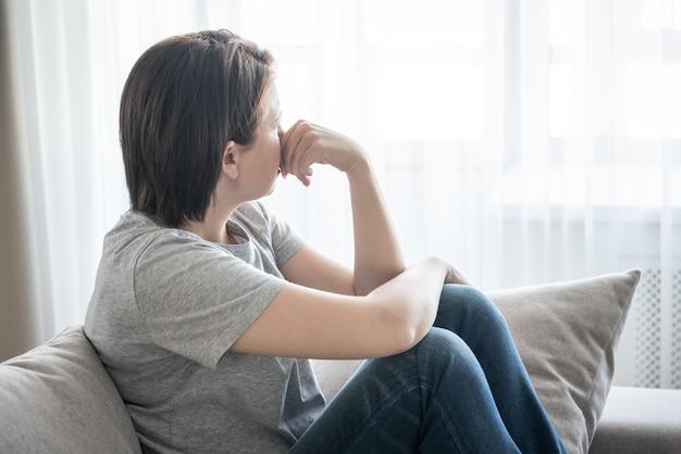 Smutna dziewczyna siedzi na kanapie w domu, problemowy pojęcie