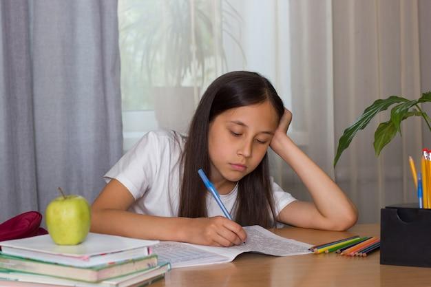 Smutna dziewczyna siedzi przy stole w domu, odrabiając lekcje pracy domowej powrót do koncepcji szkoły