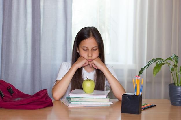 Smutna dziewczyna siedzi w domu przy stole podpiera twarz rękami patrzy na jabłko wraca do szkoły