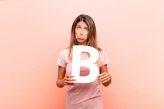 Smutna dziewczyna trzyma literę b alfabetu, aby utworzyć słowo lub zdanie