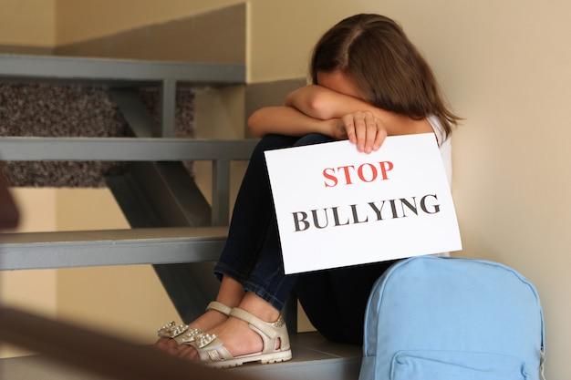 """Smutna dziewczyna trzyma znak """"stop bullying"""""""