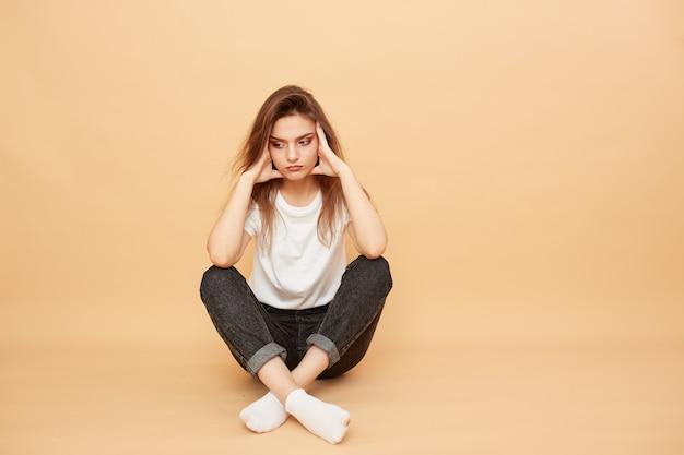Smutna dziewczyna ubrana w białą koszulkę, jeansy i białe skarpetki siedzi na podłodze na beżowym tle w studio.