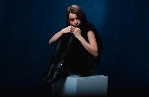Smutna dziewczyna w czarnych ubraniach, ze skrzyżowanymi nogami, siedzi na białym bloku