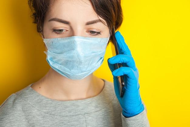 Smutna dziewczyna w masce i rękawiczkach medycznych trzyma telefon komórkowy. połączenie alarmowe z pogotowiem ratunkowym i infolinią. kwarantanna z powodu szybkiego rozprzestrzeniania się pandemii koronawirusa. zostań w domu.