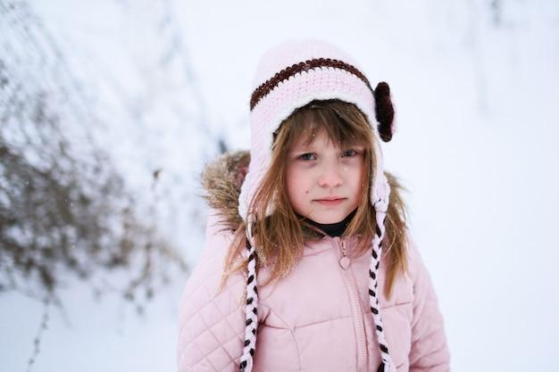 Smutna dziewczyna w różowej kurtce delikatnie marznie na zewnątrz w zimie, śnieg, pojęcie emocji