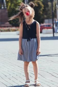 Smutna dziewczynka na ulicy z nos klauna