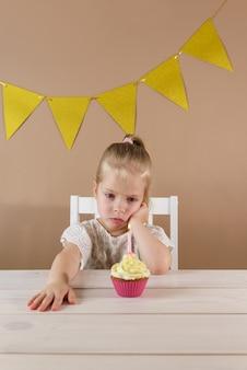 Smutna dziewczynka patrzy na ciastko ze świecą