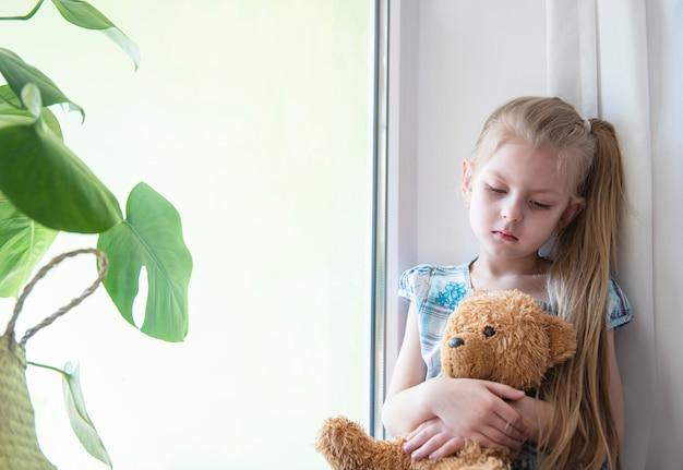 Smutna dziewczynka przy oknie