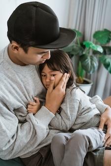 Smutna dziewczynka spoczywa na piersi ojca