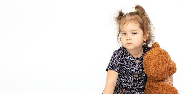 Smutna dziewczynka trzyma pluszowego misia na białym tle na białym tle dla koncepcji limitu czasu lub emocji.