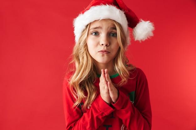 Smutna dziewczynka ubrana w boże narodzenie kapelusz stojący na białym tle, prosząc o prezent