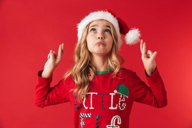Smutna dziewczynka ubrana w świąteczny kapelusz stojący na białym tle, kciuki za szczęście