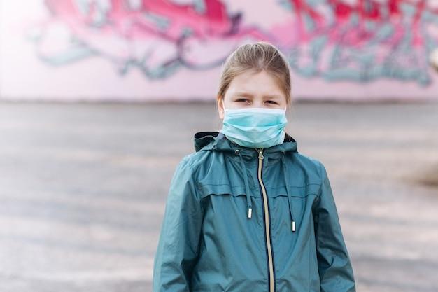 Smutna dziewczynka w sterylnych medycznych ochrony przed maską wirusa na zewnątrz. pojęcie opieki zdrowotnej, epidemii, pandemii, choroby